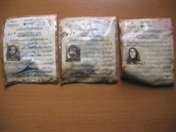 Identification cards of a woman and her two children found in a mass grave in northern Iraq.