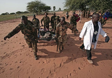 A wounded AMIS peacekeeper is carried to a helicopter at Haskanita military group site. � 2007 Reuters