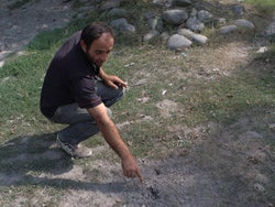 Zviad Geladze, 38, points to a cluster munition strike on the path to his farm field