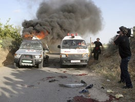 An ambulance passes by the burning vehicle of Reuters cameraman Fadel Shana after he was killed in Gaza on April 16, 2008. � 2008 Reuters