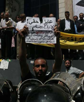 Muhammad Al-Sharqawi protests in front of the Press Syndicate in Cairo, May 25, 2006, about an hour before his arrest. The sign reads