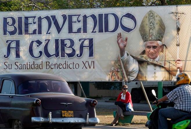 Una mujer sentada debajo de un anuncio panorámico del Papa Benedicto XVI en La Habana, Cuba el 23 de marzo de 2012. © 2012 Reuters