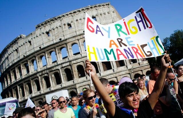 Una donna con un cartello davanti al Colosseo durante il gay pride del 15 giugno 2013 a Roma.  © 2013 Reuters