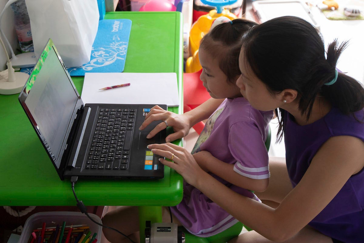 A schoolgirl taking online classes with her mother at home