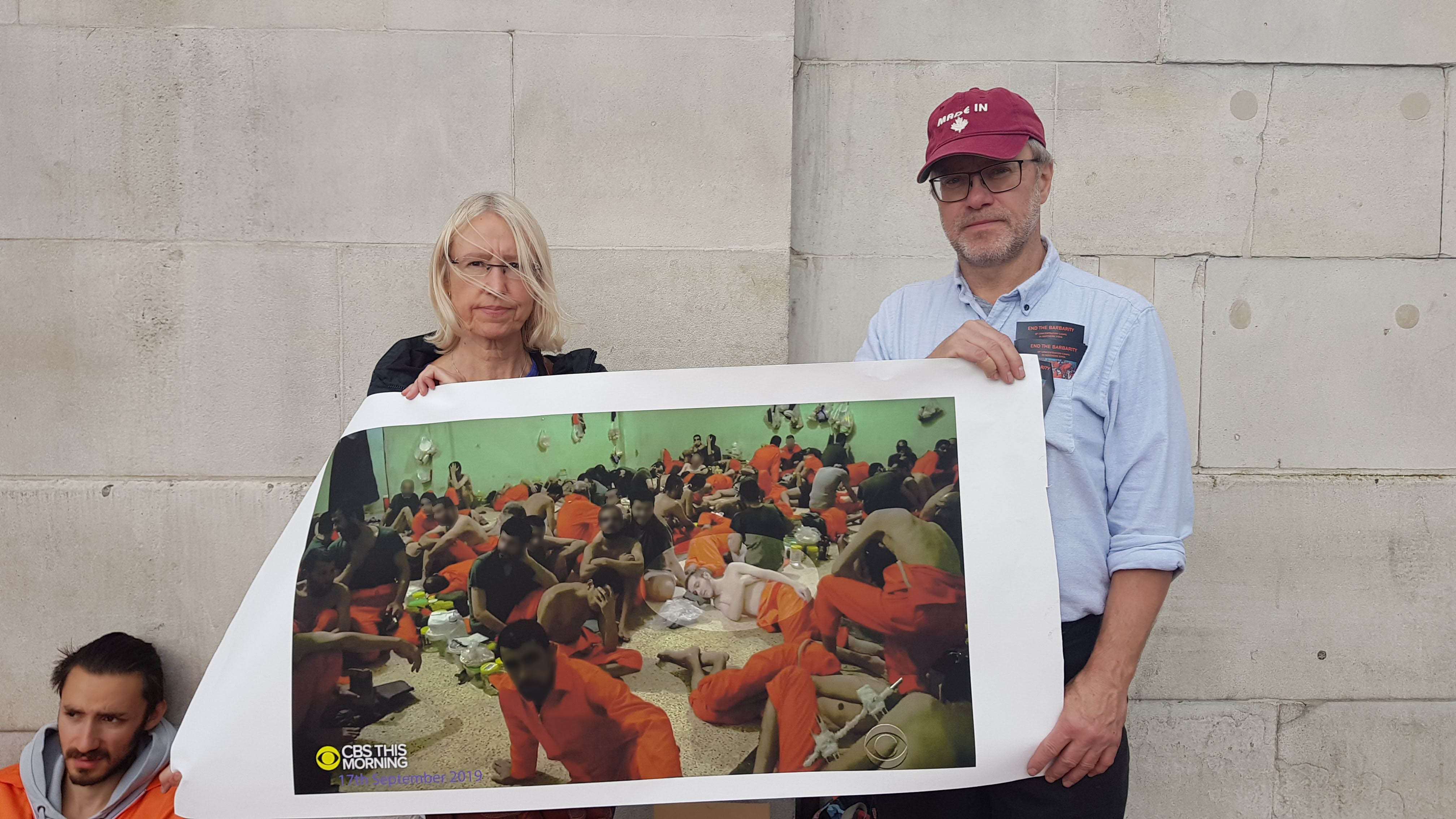 A man and woman hold up a poster of ISIS prisoners