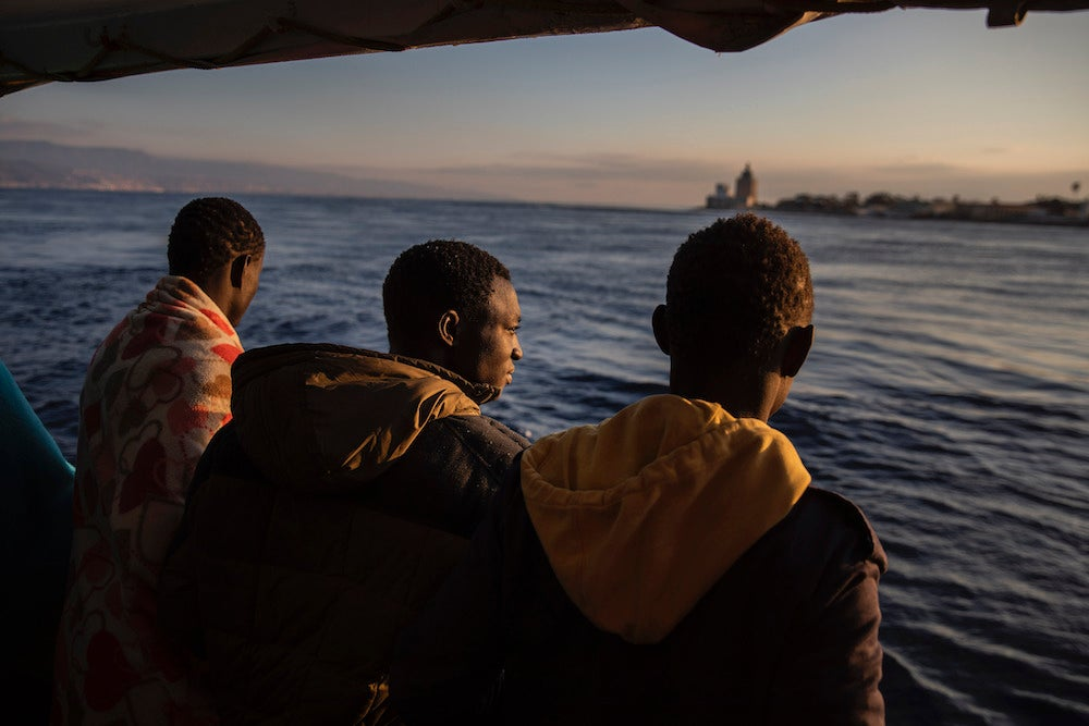 Men who were rescued off the Libyan coast in January, 2020 watch the city of Messina, Sicily from the deck of the Open Arms rescue vessel.