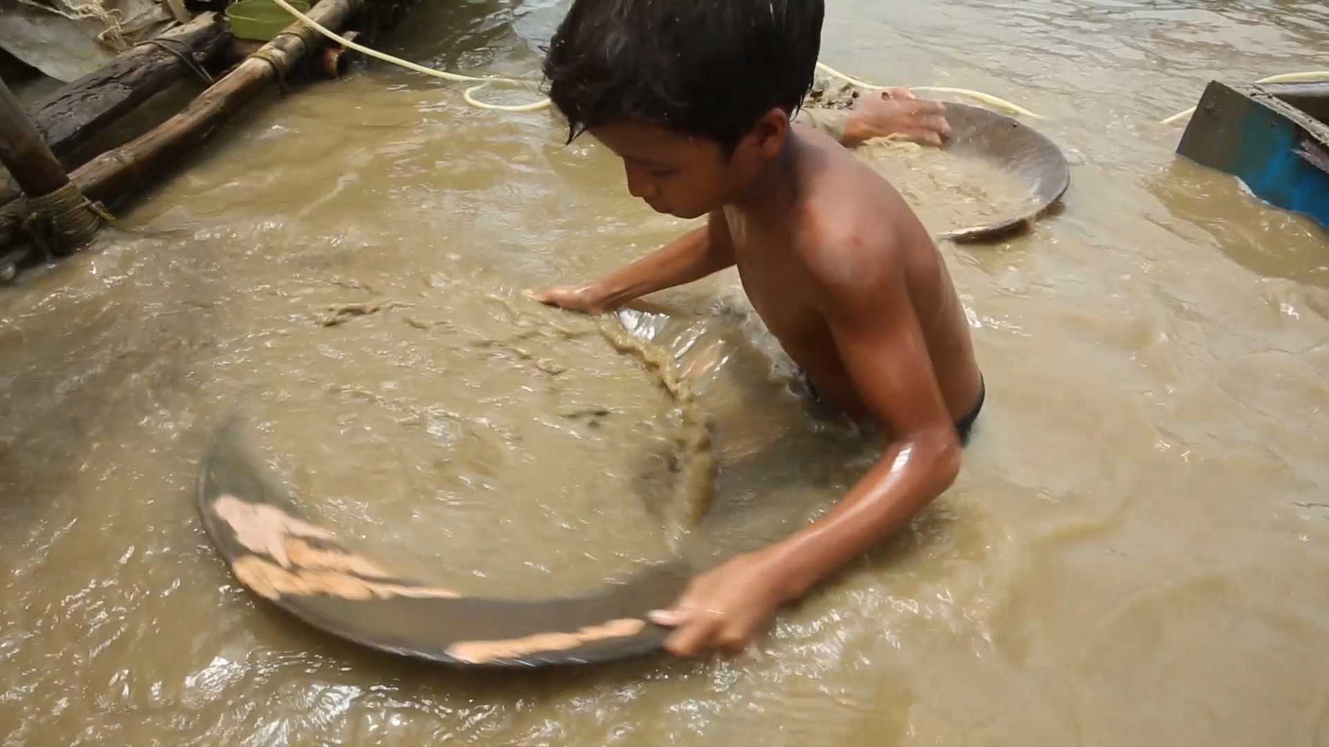 Child sifting for minerals in river