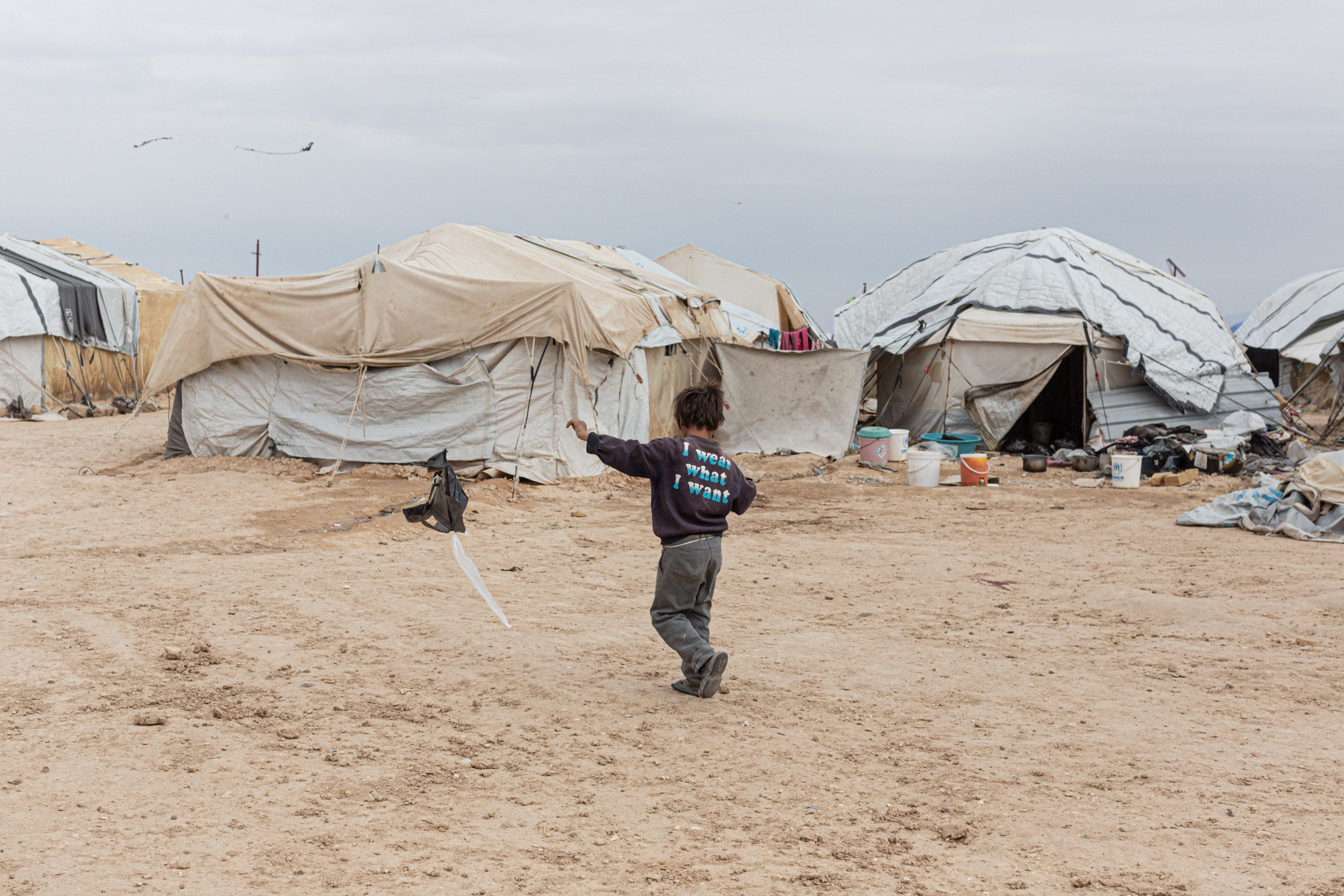 A boy flies a home-made kite in the foreigners' section of al-Hol camp in northeast Syria on March 15, 2021.
