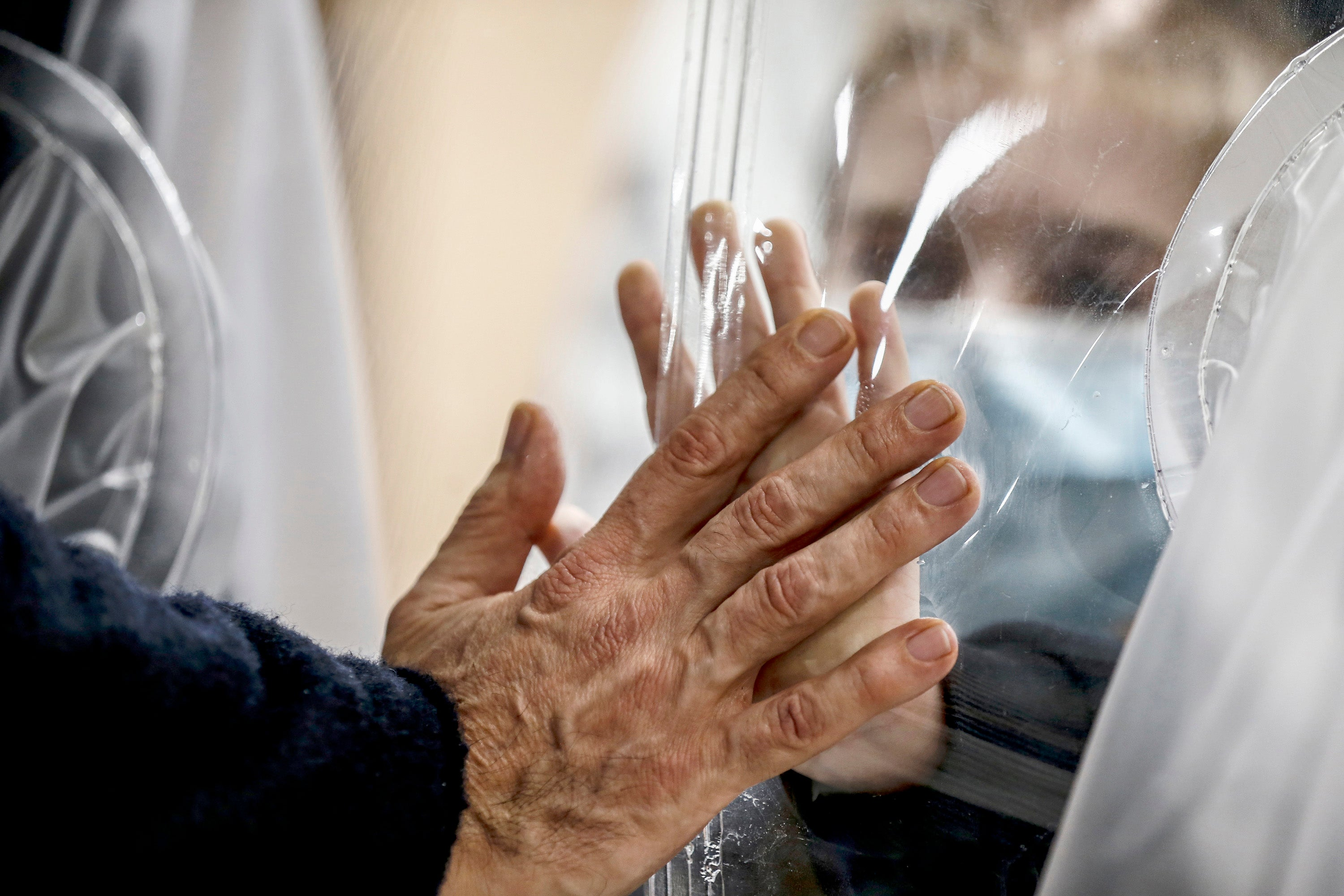 Relatives touch each other's hand through a plastic film screen and a glass to avoid contracting Covid-19 at the San Raffaele center in Rome, Italy, Dec. 22, 2020