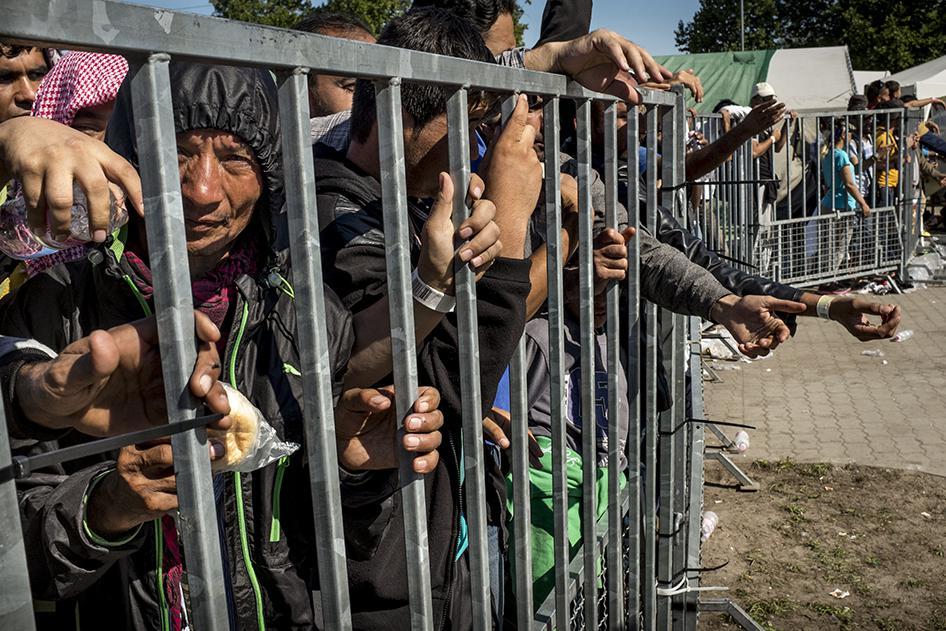 Беженцы за металлической оградой в миграционном лагере «Хангар 1» в городе Рожке, Венгрия, 9 сентября 2015 года.