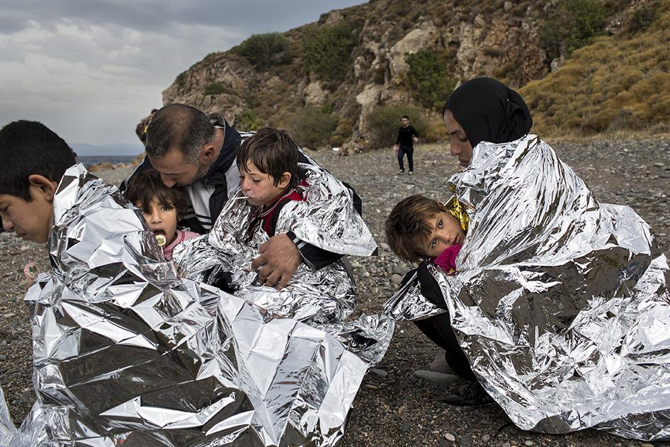 A family sits on the shore of the Greek island of Lesbos wrapped in thermal blankets after journeying from Turkey aboard a rubber boat. October 11, 2015. © 2015 Zalmaï for Human Rights Watch