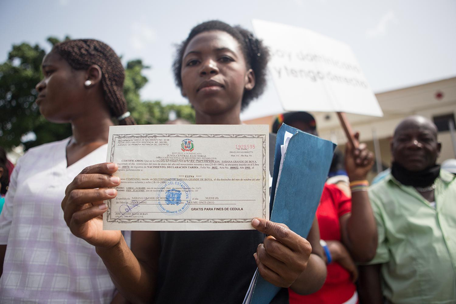 Elena Lorac, a spokesperson from the Reconoci.do movement, shows a birth certificate issued by the Central Electoral Board, during a rally in front of the Presidential Palace in Santo Domingo, July 12, 2013.