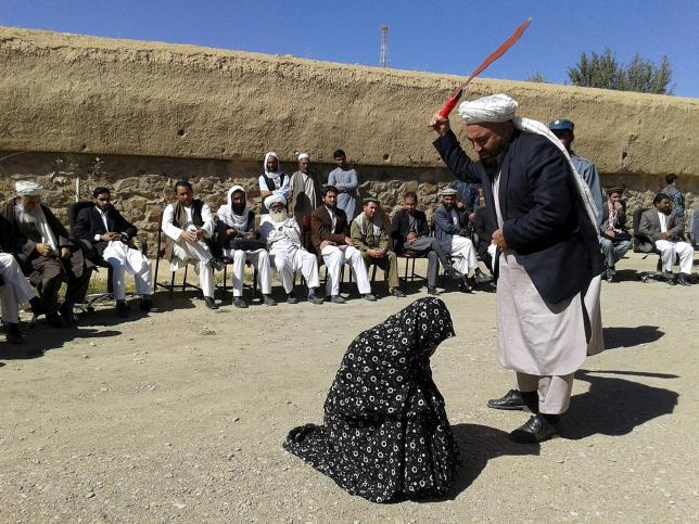 An Afghan judge hits a woman with a whip in front of a crowd in Ghor province, Afghanistan August 31, 2015.