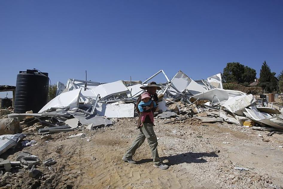 A Palestinian Bedouin carries his child as he walks past his caravan that was demolished by Israeli bulldozers near the Israeli settlement of Karmel, in the village of Um Alkhier near the West Bank city of Hebron October 27, 2014.