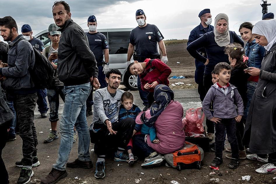 Menedékkérök és migránsok várakoznak gyermekeikkel a magyar-szerb határon található röszkei gyüjtöpontnál rendöri felügyelet mellett, hogy buszokra szállhassanak, amelyek az ideiglenes befogadóközpontokba szállítják öket. Röszke, Magyarország. 2015, Szept