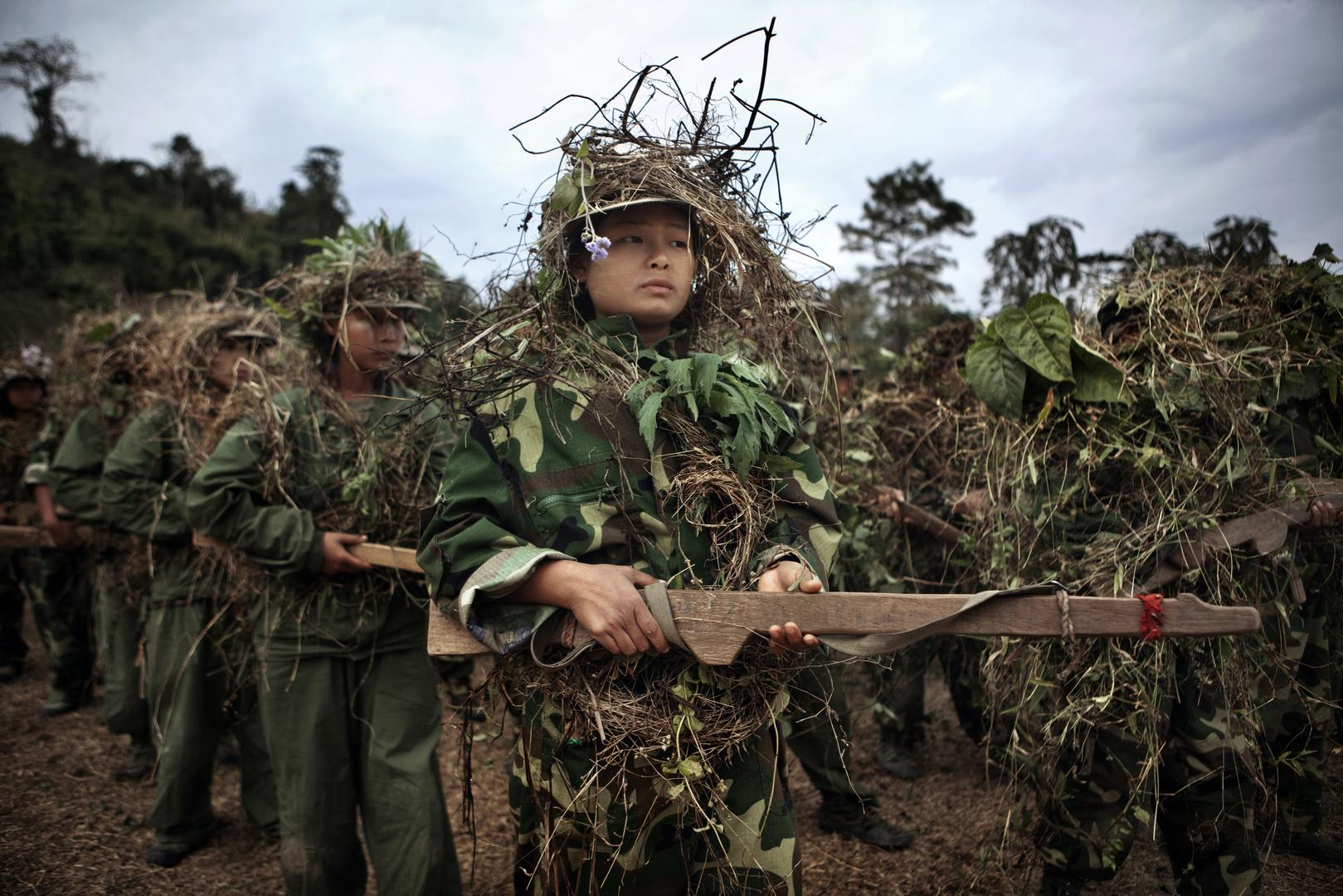 Kachin Independence Army (KIA) and militia trainees wearing camouflage and carrying wooden guns during a three-month basic training course near Laiza in KIA-controlled territory of Kachin State, January 2012.