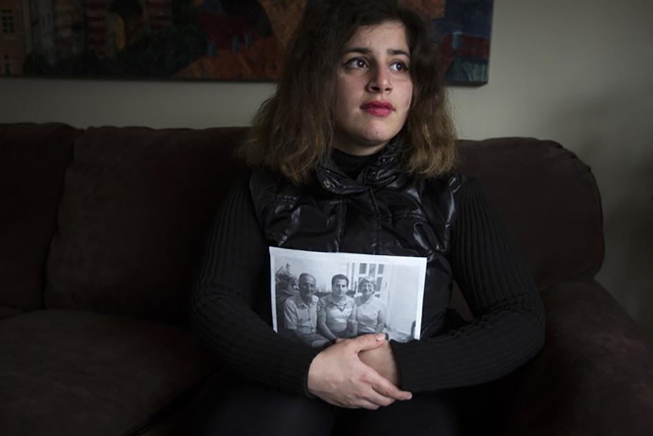 Refugiada recém-chegada da Síria, Sandy Khabbazeh, segura um retrato com uma foto de sua família que ficou para trás na Síria. Oakland, New Jersey. 22 de novembro de 2015.