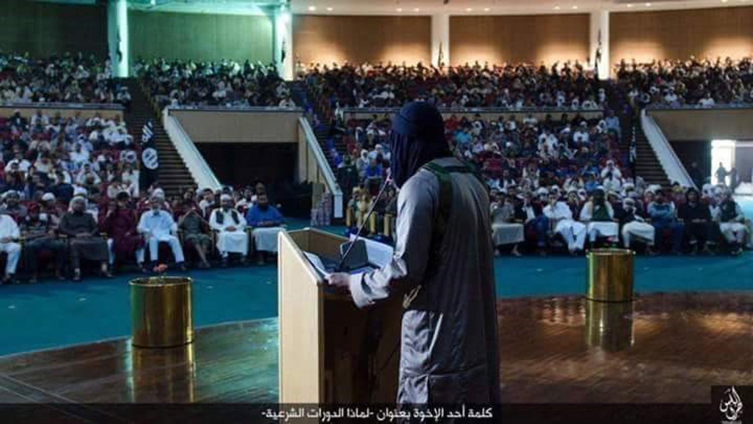 "An ISIS lecture on Sharia (Islamic law) at the Ouagadougou complex in Sirte, Libya, where former Libyan leader Muammar Gaddafi once hosted summits with world leaders. The caption in Arabic reads: ""Speech by one of the brothers (why we are holding Sharia s"
