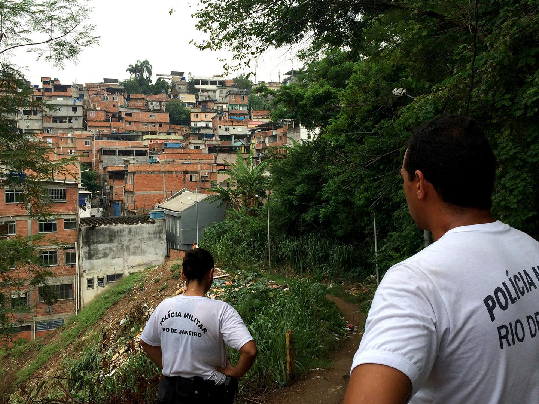 Os policiais militares Roberta Moreira (esq.) e Wallace Justo (dir.) caminham em uma das trilhas na favela da Mangueira em 14 de janeiro de 2016.