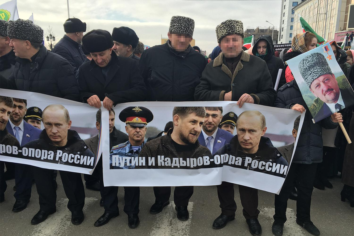"Men carrying a banner reading ""Putin and Kadyrov are Russia's foundation"". Grozny, Chechnya, January 2016."