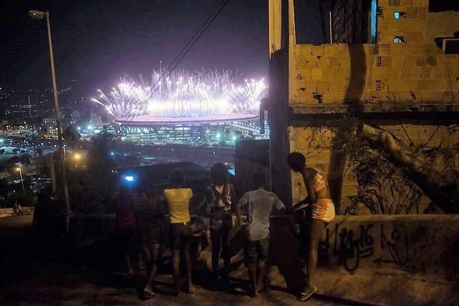 Moradores da favela da Mangueira assistem aos fogos de artifício durante abertura a cerimônia de abertura dos Jogos Olímpicos no estádio do Maracanã, no Rio de Janeiro.