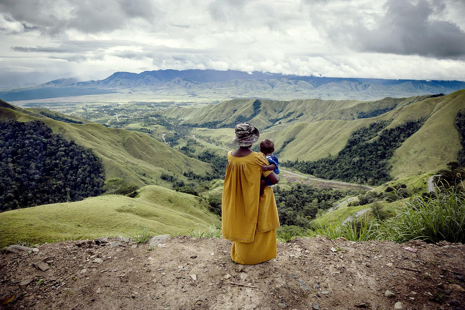 A woman holding a child looks down the valley from Kassam Pass, in Papua New Guinea's Highlands, an isolated region where some people must walk several days to reach the nearest road.   © 2012 Vlad Sokhin/Panos