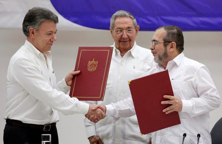 Presidente de Cuba, Raul Castro (centro), Presidente da Colômbia, Juan Manuel Santos (esq.) e líder das FARC, Rodrigo Londono, mais conhecido por seu nome de guerra, Timochenko, reagem após a assinatura de um histórico acordo de cessar-fogo.