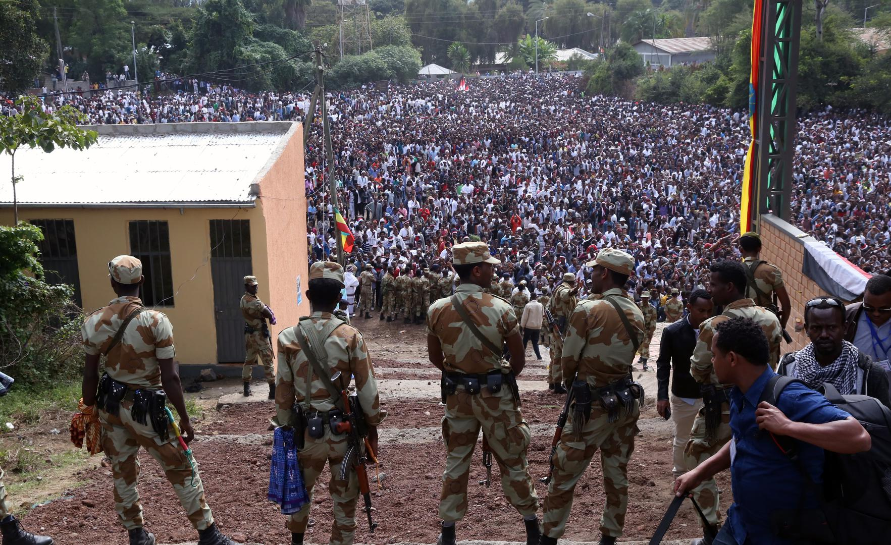 Armed security officials watch as protesters stage a protest against government during the Irreechaa cultural festival in Bishoftu, Ethiopia on October 02, 2016.