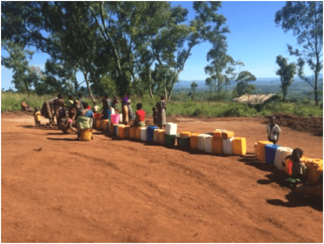 Women and girls at one of the two only borehole wells at the crowded Kapise camp in Malawi that is now serving over 6000 people.