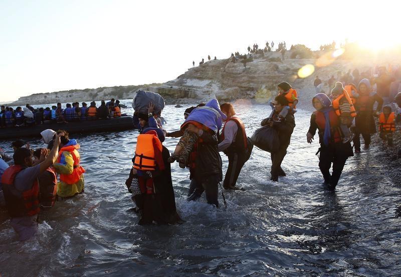 Flüchtlinge mit ihren Kinder gehen zu einem Schlauchboot, um von Cesme in der Türkei auf die griechische Insel Chios zu segeln.
