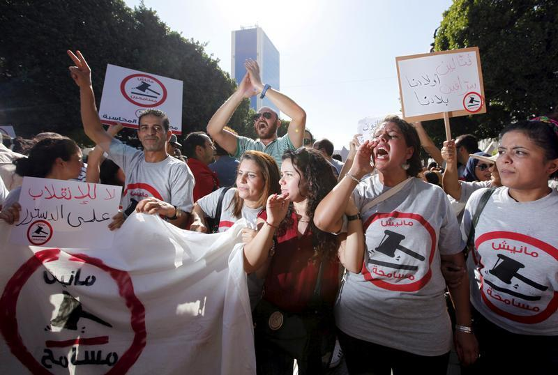 Protesters shout slogans during a demonstration against the economic reconciliation bill at Bourguiba Avenue in Tunis