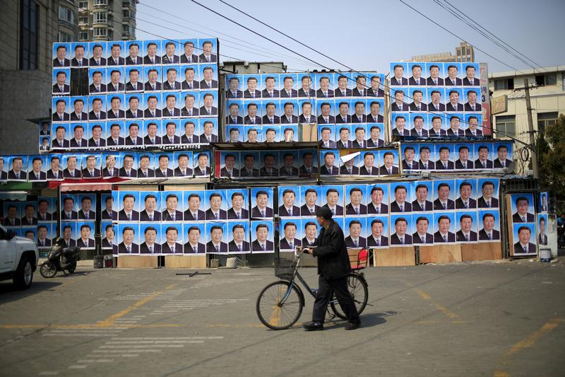 A man with a bicycle walks past a building covered in posters of Chinese President Xi Jinping in Shanghai, China, on March 26, 2016.