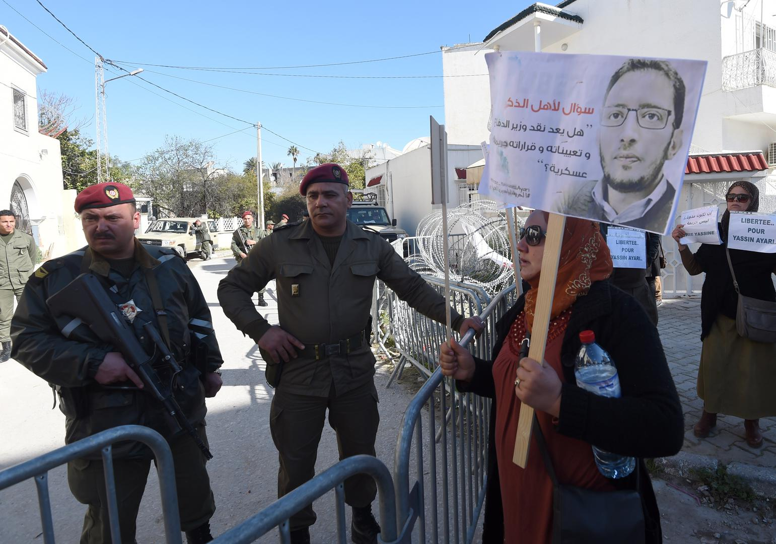 Tunisian protesters stand outside a military court in Tunis as they demonstrate in support of blogger Yassine Ayari during his appeal hearing on March 3, 2015.