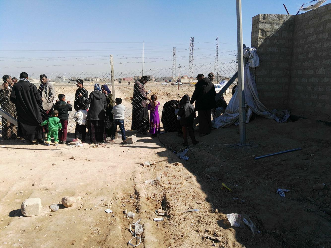 Residents of Shahama camp speak with relatives through the camp fence.