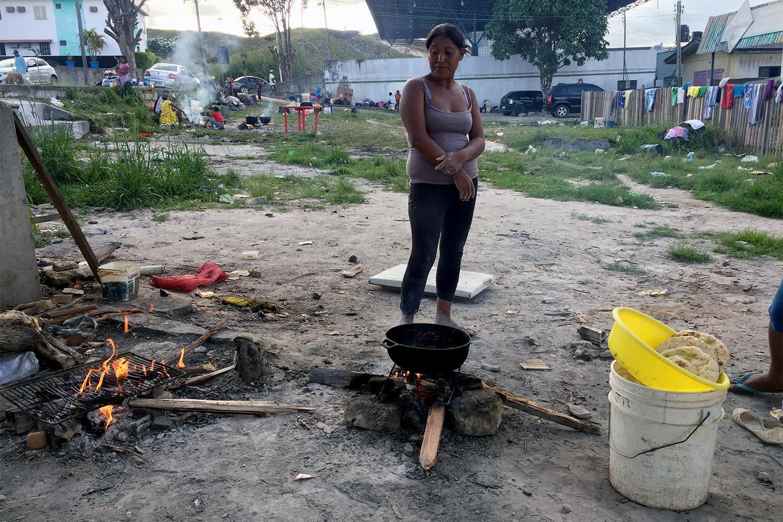 Uma venezuelana da etnia indígena Warao cozinha em um terreno baldio ao lado da rodoviária de Pacaraima, Brasil, onde mora com cerca de 100 outros membros de sua comunidade. 12 de fevereiro de 2017.