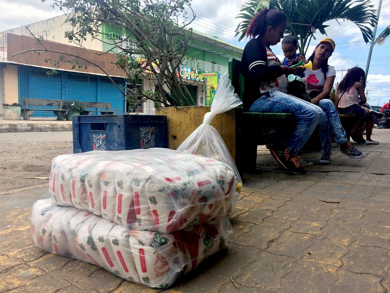 Sacos de arroz vendidos na rua na cidade fronteiriça brasileira de Pacaraima. Muitos venezuelanos atravessam para o Brasil para comprar alimentos e remédios que não conseguem encontrar ou pagar na Venezuela. 12 de fevereiro de 2017.