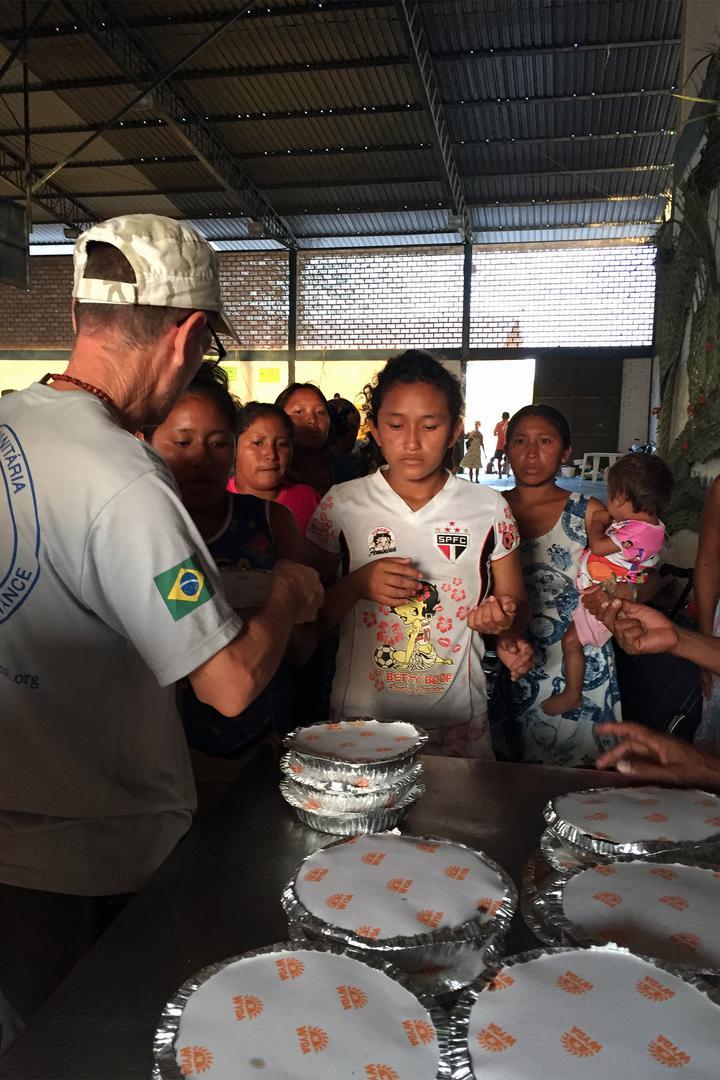 Membros da equipe da Fraternidade, uma organização internacional de ajuda humanitária, distribuem refeições em um abrigo em Boa Vista, onde mais de 180 venezuelanos viviam em fevereiro de 2017. 11 de fevereiro de 2017.