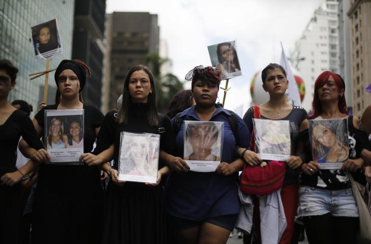 Women hold pictures of victims that died of domestic abuse against women, during a march to celebrate International Women's Day in Sao Paulo March 8, 2014.