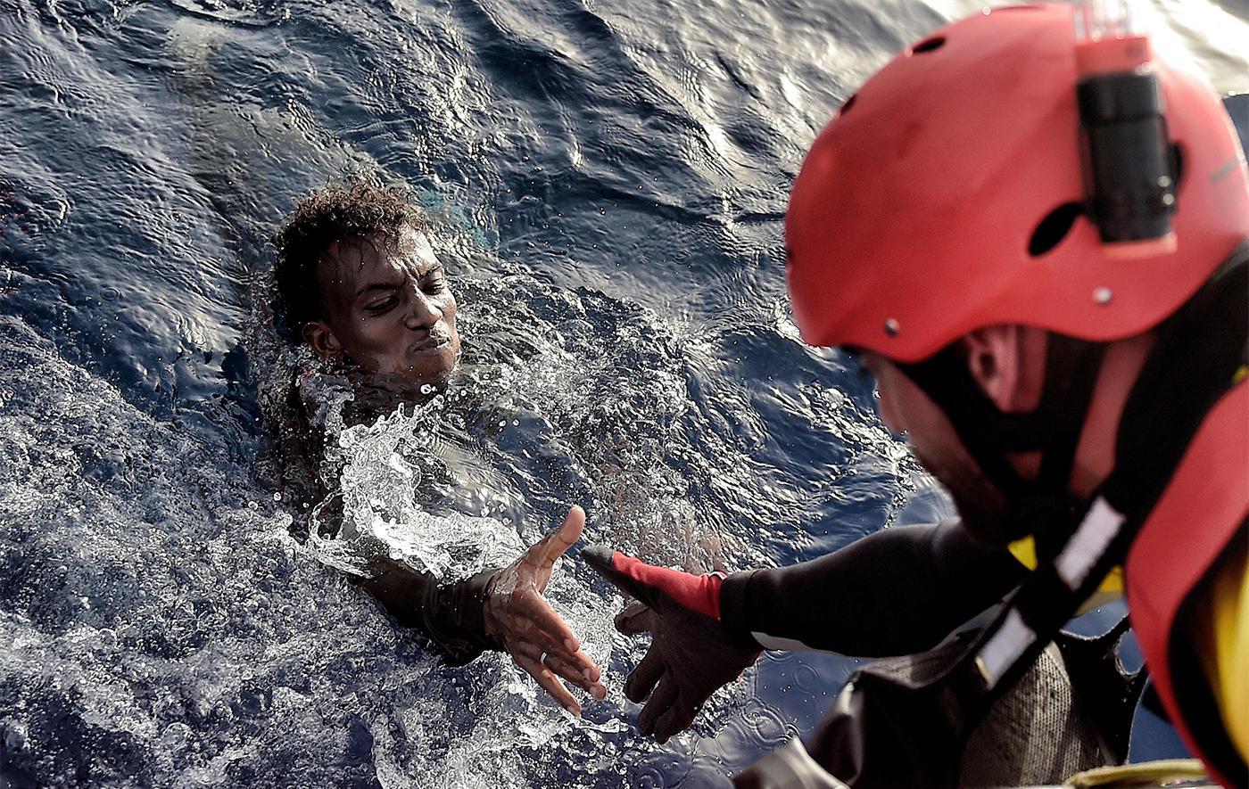 Ein Migrant wird am 3. Oktober 2016 von einem Mitglied der Nichtregierungsorganisation Proactive Open Arms aus dem Mittelmeer, etwa 20 Meilen nördlich von Libyen, gerettet.