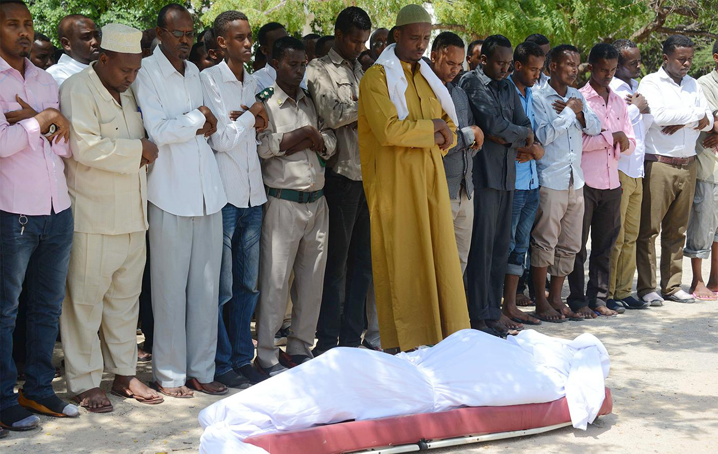 Relatives and fellow journalists pray over the body of Somali journalist Yusuf Keynan, on June 21, 2014, during his funeral. Keynan died in Mogadishu after a bomb believed to have been attached to his car was remotely detonated.