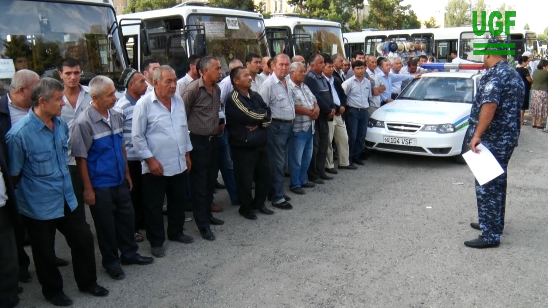 Police instructing bus drivers waiting to transport students from Andijan State University to the cotton fields, September 2015.