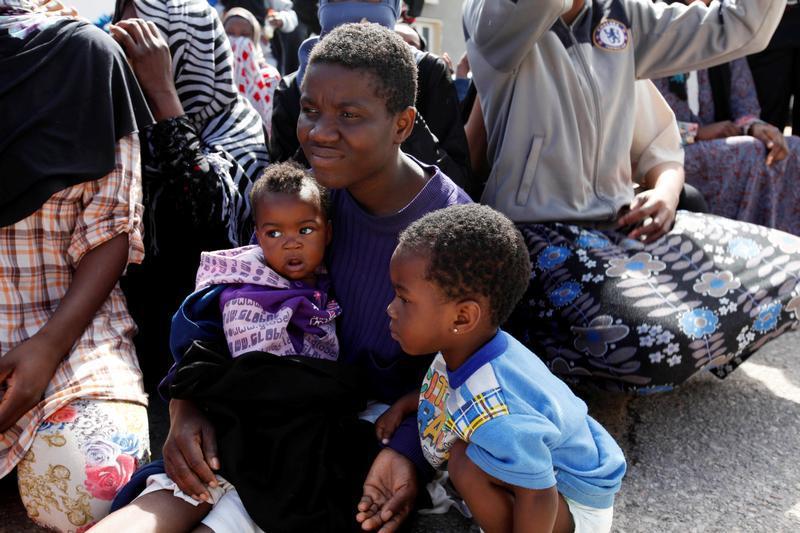 Ein Mann mit seinen Kindern in einem Internierungscamp in Tripolis, Libyen, während des Besuchs des UN-Sonderbeauftragten und Leiters der UN-Mission in Libyen, Martin Kobler, sowie des Direktors der Internationalen Organisation für Migration, William Lacy