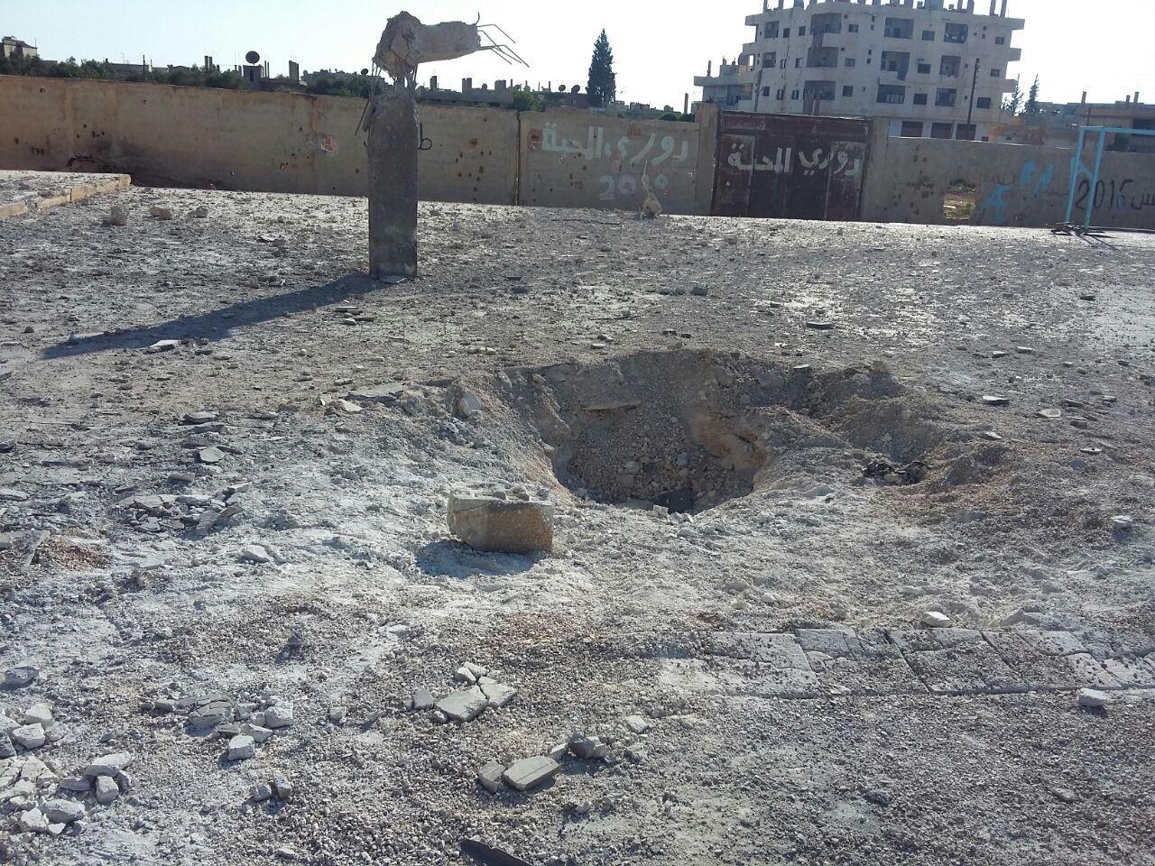 الحفرة التي خلفتها الغارة الجوية السورية-الروسية في 14 يونيو/حزيران 2017 في ساحة مدرسة الشهيد كيوان. 7 من أصل 8 ضحايا، بينهم طفل، ينتمون إلى عائلة نازحة كانت تتخذ من المدرسة ملجأ.