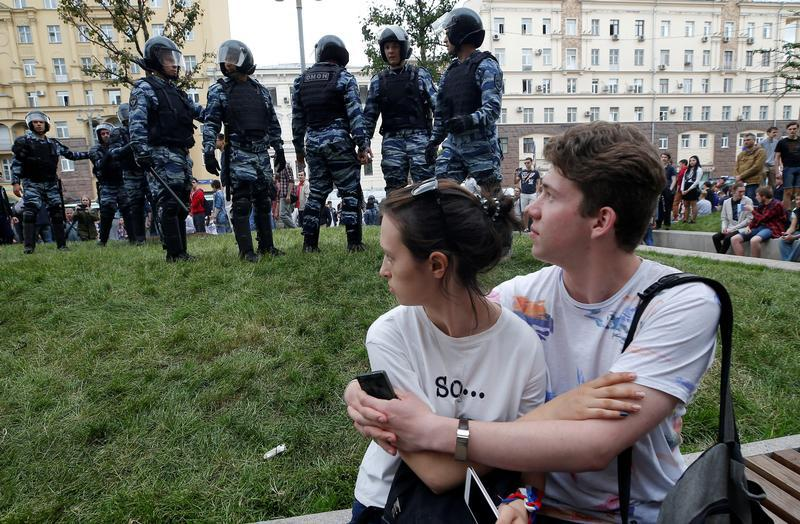 A couple sits in front of riot police standing guard during an anti-corruption protest organised by opposition leader Alexei Navalny, on Tverskaya Street in central Moscow, Russia, June 12, 2017.