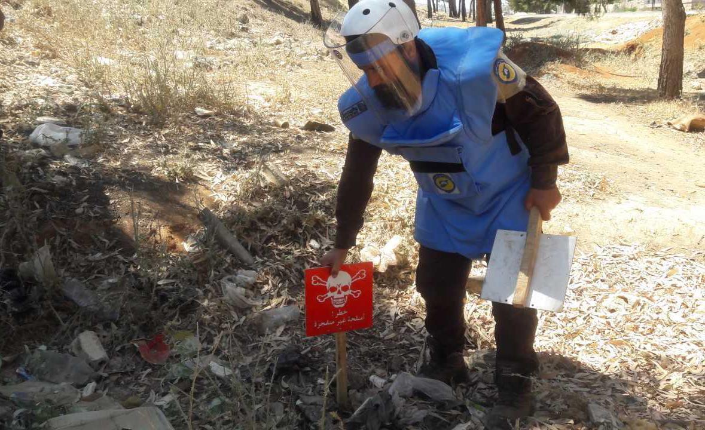 """Técnico treinado da Defesa Civil Síria (""""capacetes brancos"""") identifica e marca submunição intacta e outros remanescentes de explosivos da guerra para limpeza e destruição em Idlib em 8 de Junho de 2017."""
