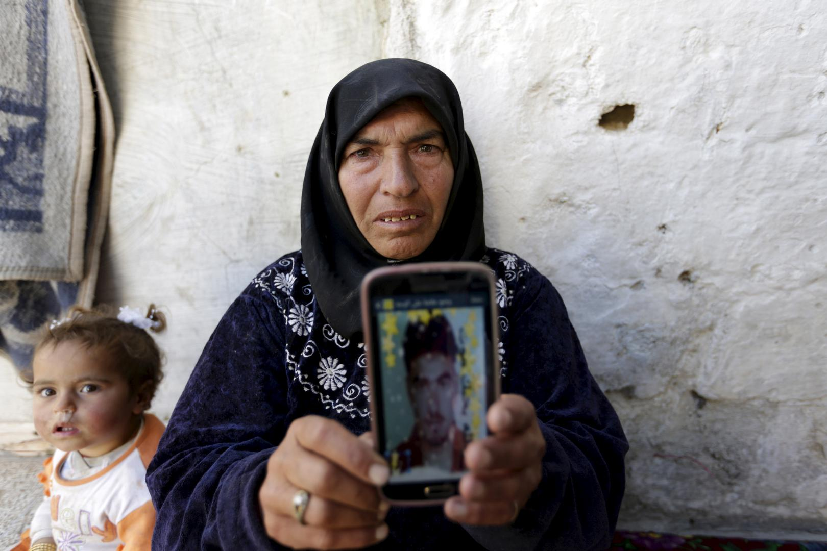 A mother shows a picture of her son, who was detained by authorities in the northern Syrian province of Idlib, Syria, March 20, 2016. She has not heard any news about her son since then.