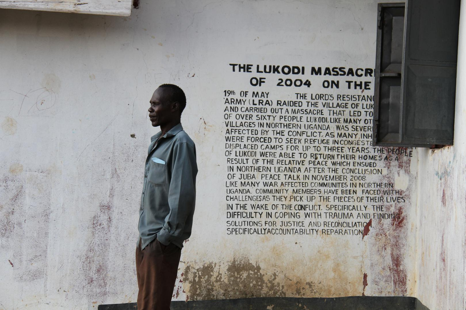 A community member in Lukodi stands next to a memorial of a May 19, 2004 massacre, one of the atrocities for which Dominic Ongwen is facing charges before the International Criminal Court. Over 4,000 victims are participating in the trial. ©2016 G. GT.