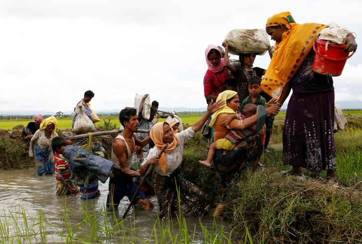 A group of Rohingya refugees cross a canal after travelling over the Bangladesh-Burma border in Teknaf, Bangladesh, September 1, 2017.