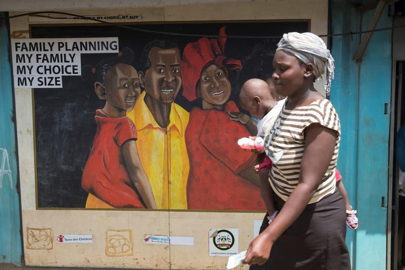 A woman walks past a mural on a Family Health Options clinic in the Kibera slums in Nairobi, Kenya, May 16, 2017. © 2017 Reuters