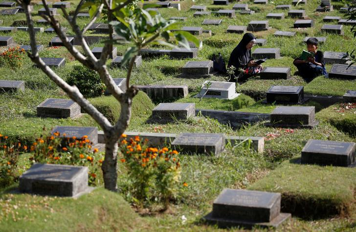 201711Asia_Indonesia_1965 Two people pray at the grave of a loved one in Jakarta, Indonesia, June 26, 2017.